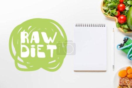 Foto de Vista superior de cuaderno en blanco cerca de alimentos de dieta y saltar la cuerda sobre fondo blanco con letras de dieta cruda - Imagen libre de derechos