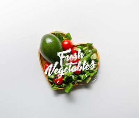 Photo for Top view of fresh green vegetables in heart shaped bowl on white background with fresh vegetables lettering - Royalty Free Image
