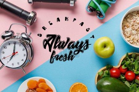 Widok z góry na pyszne potrawy dietetyczne i sprzęt sportowy z budzikiem na niebieskim i różowym tle ze śniadaniem zawsze świeże napis