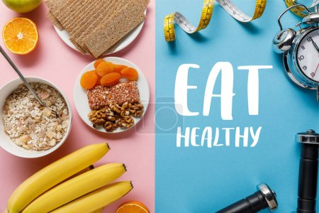 Photo for Top view of fresh fruits, crispbread and breakfast cereal on pink and dumbbells and measuring tape on blue background with eat healthy lettering - Royalty Free Image