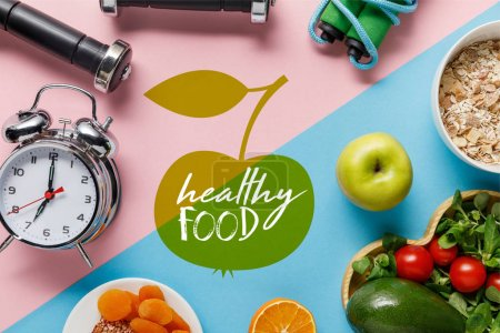 Photo for Top view of delicious diet food and sport equipment with alarm clock on blue and pink background with healthy food lettering - Royalty Free Image