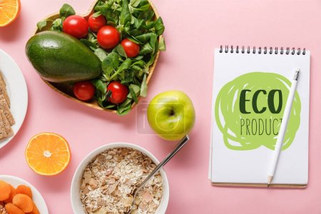 Foto de Top view of fresh diet food and notebook with eco product lettering on pink background - Imagen libre de derechos