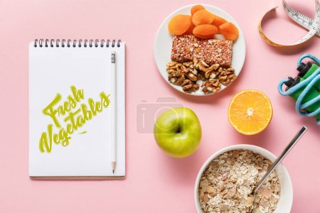 Photo for Top view of fresh diet food, measuring tape, skipping rope and notebook with fresh vegetables lettering on pink background with copy space - Royalty Free Image