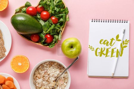 Photo for Top view of fresh diet food and notebook with eat green lettering on pink background - Royalty Free Image