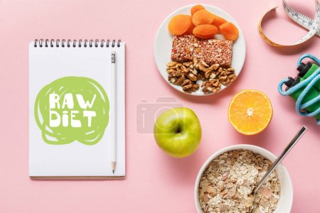 Foto de Top view of fresh diet food, measuring tape, skipping rope and notebook with raw diet lettering on pink background with copy space - Imagen libre de derechos