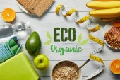 """Постер, картина, фотообои """"top view of diet food near measuring tape and sport equipment on wooden white background with eco organic lettering"""""""