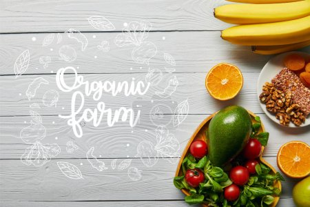 Photo for Top view of fresh fruits, vegetables in heart-shaped bowl on wooden white background with organic farm lettering - Royalty Free Image