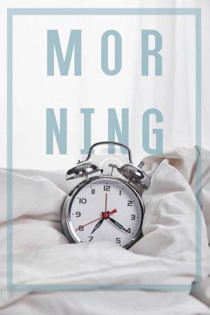 Foto de Reloj despertador de plata en manta en cama blanca con ilustración de la mañana - Imagen libre de derechos