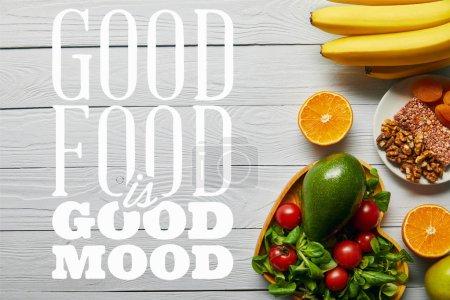 Photo pour Vue supérieure des fruits frais, légumes dans le bol en forme de coeur sur le fond blanc en bois avec la bonne nourriture est le lettrage de bonne humeur - image libre de droit