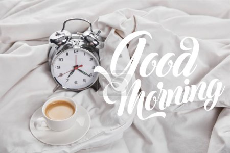 Photo for Coffee in white cup on saucer near silver alarm clock in bed with good morning illustration - Royalty Free Image