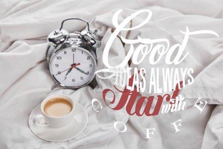 Foto de Coffee in white cup on saucer near silver alarm clock in bed with good ideas always start with coffee illustration - Imagen libre de derechos