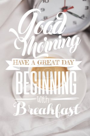 Photo for Top view of coffee in white cup on saucer near silver alarm clock on bedding with good morning, have a great day beginning with breakfast lettering - Royalty Free Image