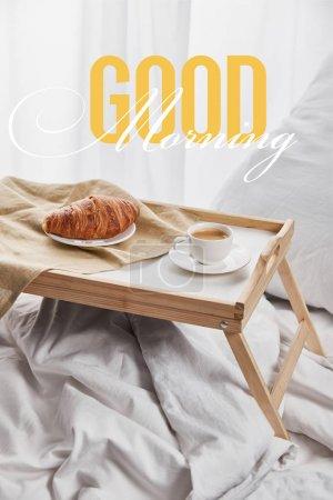 Foto de Café y croissant servido en bandeja de madera en la cama blanca con almohada con ilustración de buenos días - Imagen libre de derechos