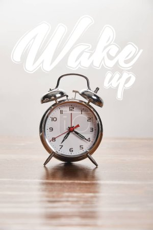 Photo for Silver alarm clock on wooden table isolated on grey with wake up illustration - Royalty Free Image