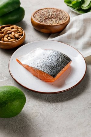 Photo for Fresh raw salmon on white plate near nuts and avocado, ketogenic diet menu - Royalty Free Image