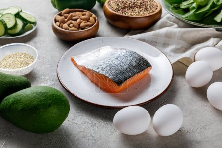Photo for Fresh raw salmon on white plate near eggs, nuts and avocado, ketogenic diet menu - Royalty Free Image