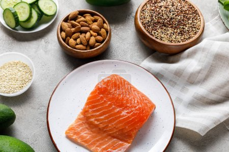 top view of fresh raw salmon on white plate near nuts and vegetables, ketogenic diet menu