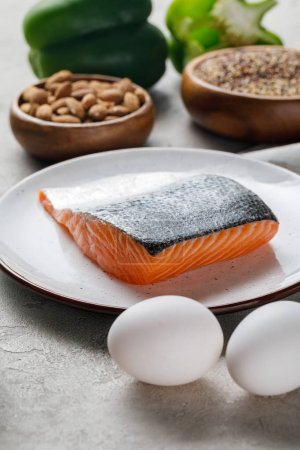 Photo for Selective focus of fresh raw salmon on white plate near nuts and eggs, ketogenic diet menu - Royalty Free Image