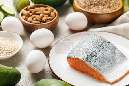 Photo for Fresh salmon on white plate near nuts and eggs, ketogenic diet menu - Royalty Free Image