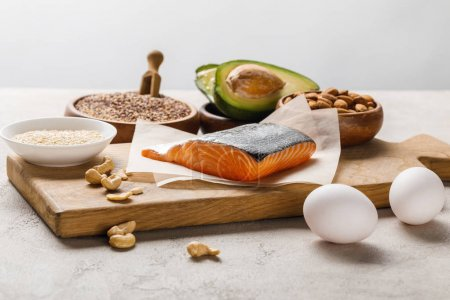 Photo for Fresh salmon, nuts, eggs and avocado on wooden chopping board near oil isolated on grey, ketogenic diet menu - Royalty Free Image