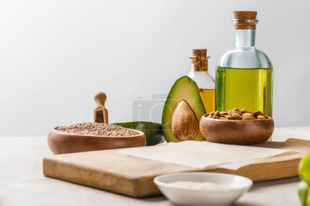 Photo for Nuts and avocado on wooden chopping board near oil and groats isolated on grey, ketogenic diet menu - Royalty Free Image