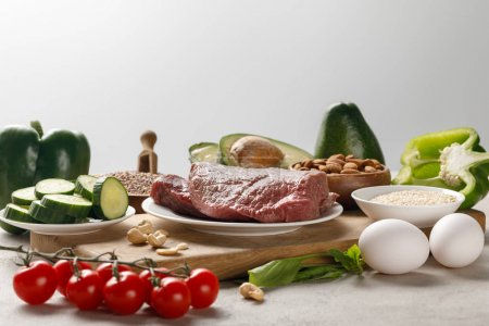 Photo for Fresh raw meat on wooden chopping board near nuts and vegetables isolated on grey, ketogenic diet menu - Royalty Free Image
