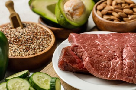 Photo for Selective focus of raw meat near nuts, groats and green vegetables, ketogenic diet menu - Royalty Free Image
