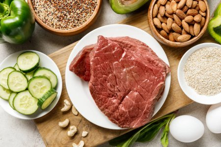 Photo for Top view of raw meat on wooden chopping board near nuts, groats, eggs and green vegetables, ketogenic diet menu - Royalty Free Image