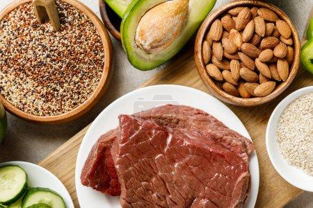 Photo for Top view of fresh raw meat on white plate near nuts, groats and avocado, ketogenic diet menu - Royalty Free Image