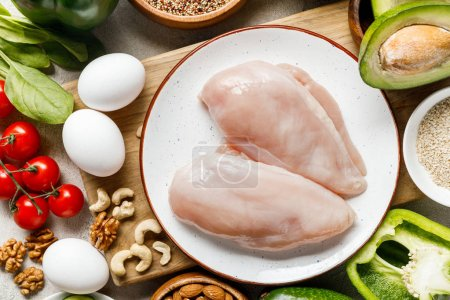 Photo for Top view of fresh raw chicken breasts on white plate near nuts, eggs and vegetables, ketogenic diet menu - Royalty Free Image