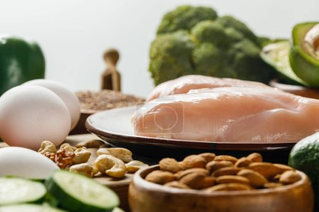 Photo for Selective focus of raw chicken breasts and eggs isolated on grey, ketogenic diet menu - Royalty Free Image
