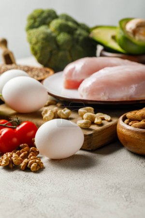 Photo for Selective focus of fresh raw chicken breasts on white plate near nuts and eggs, ketogenic diet menu - Royalty Free Image
