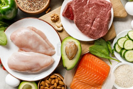 top view of fresh raw salmon, meat and chicken breasts near nuts and vegetables, ketogenic diet menu