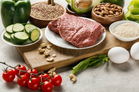 Photo for Fresh raw meat on wooden chopping board near nuts, vegetables and groats, ketogenic diet menu - Royalty Free Image