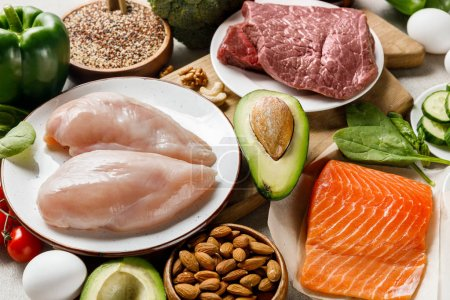 Photo for Fresh raw salmon, meat and chicken breasts near nuts and vegetables, ketogenic diet menu - Royalty Free Image