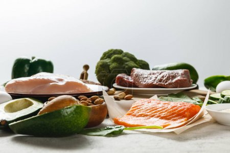 Photo for Fresh raw salmon, meat and chicken breasts near green vegetables isolated on grey, ketogenic diet menu - Royalty Free Image