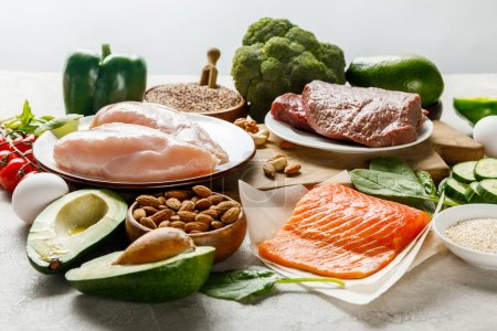 Photo for Raw salmon, meat and chicken breasts near green vegetables isolated on grey, ketogenic diet menu - Royalty Free Image