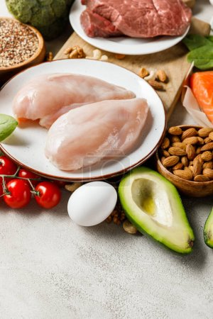 Photo for Fresh raw meat and chicken breasts near vegetables and nuts, ketogenic diet menu - Royalty Free Image