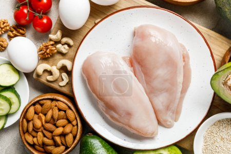 Photo for Top view of fresh raw chicken breasts near nuts, eggs and vegetables, ketogenic diet menu - Royalty Free Image