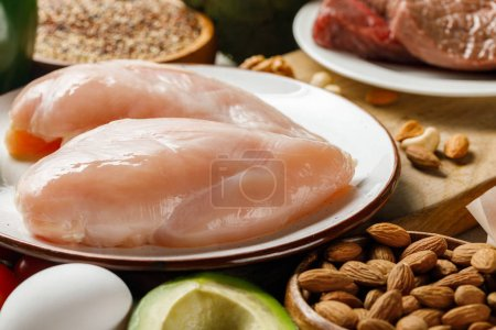 Photo for Fresh raw chicken breasts on white plate near nuts, egg and avocado, ketogenic diet menu - Royalty Free Image