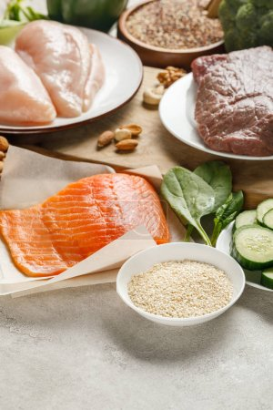 Photo for Fresh raw salmon, chicken breasts and meat near nuts, spinach, cucumbers and groats, ketogenic diet menu - Royalty Free Image