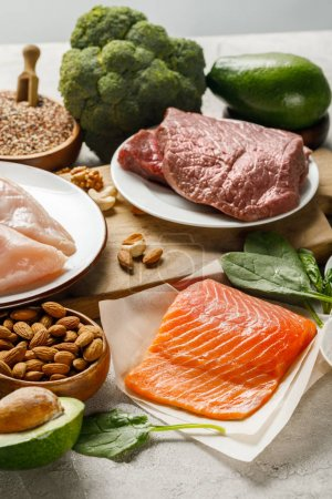 fresh raw salmon, chicken breasts and meat near nuts, broccoli and avocado, ketogenic diet menu