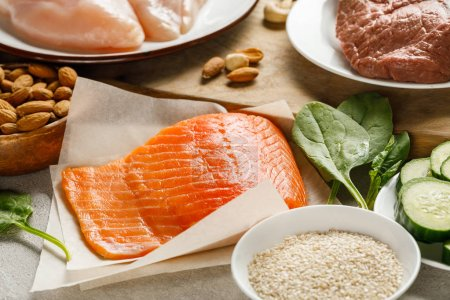 fresh raw salmon, chicken breasts and meat near nuts, spinach and groats, ketogenic diet menu