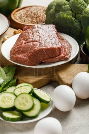 Photo for Close up view of raw meat on wooden chopping board near eggs and cucumbers, , ketogenic diet menu - Royalty Free Image