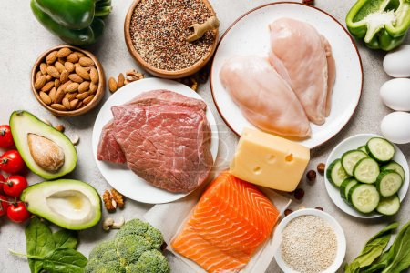Photo for Top view of raw salmon, chicken breasts and meat on white plates near nuts, eggs, cheese and vegetables, ketogenic diet menu - Royalty Free Image