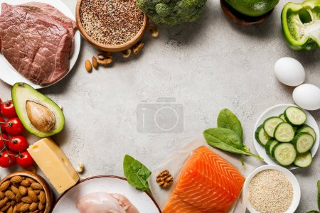 Photo for Top view of raw salmon, chicken breasts and meat near nuts, dairy products and vegetables on grey background with copy space, keto diet menu - Royalty Free Image