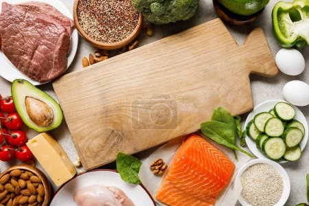 Photo for Top view of raw salmon, chicken breasts and meat near nuts, dairy products and vegetables around wooden chopping board with copy space, ketogenic diet menu - Royalty Free Image