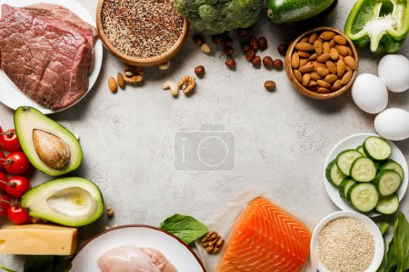 Photo for Top view of raw salmon, chicken breasts and meat near nuts, dairy products and vegetables on grey background with copy space, ketogenic diet menu - Royalty Free Image