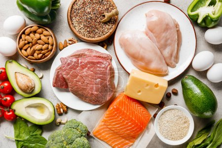 Photo for Top view of raw salmon, chicken breasts and meat on white plates near nuts, eggs and vegetables, ketogenic diet menu - Royalty Free Image