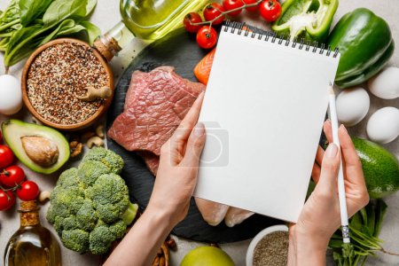 Photo for Cropped view of woman holding empty notebook above food for ketogenic diet menu - Royalty Free Image